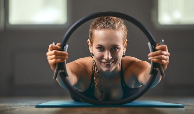 Фитнес-тренер утром показывает упражнения с эспандером в тренажерном зале. копирование пространства, фитнес-мотиватор. Premium Фотографии