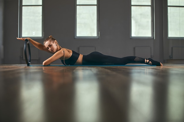 Fitness trainer with a beautiful figure poses for the camera during a workout in the gym with an ispander ring Premium Photo