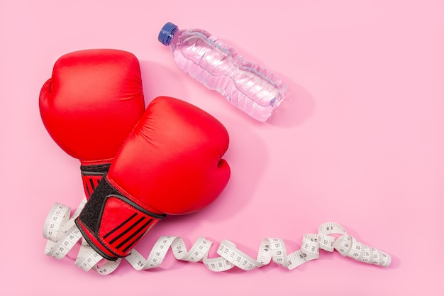 Fitness, weight loss or exercise concept. boxing gloves, mineral water and measure tape isolated Premium Photo