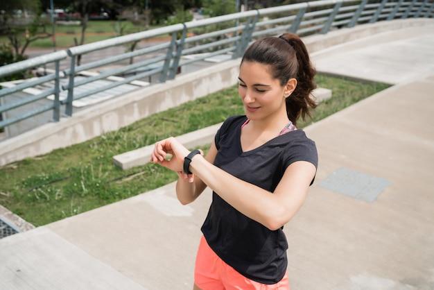フィットネス女性がスマートな時計で時間をチェック 無料写真