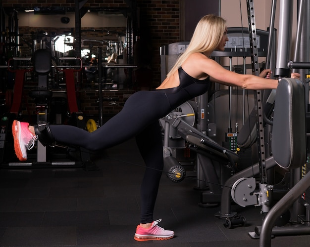 Fitness woman doing a leg rise in gym Premium Photo