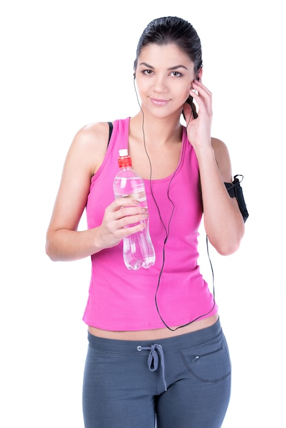 Fitness woman drinking water and listening to music. Premium Photo