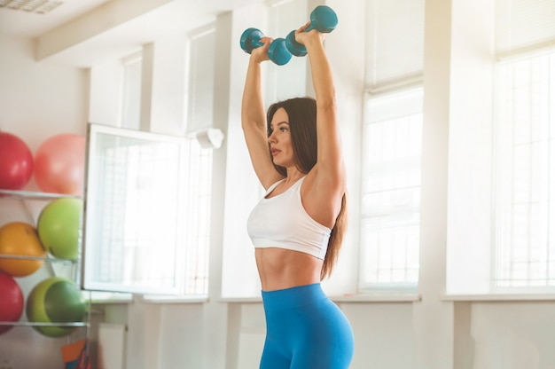 Fitness woman holding dumbbells Premium Photo