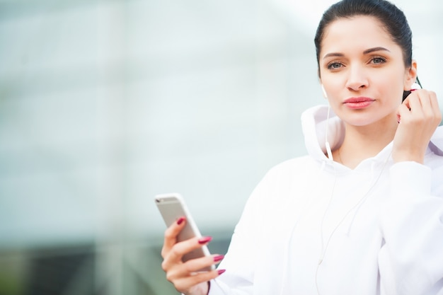 Fitness. woman listening music on phone while exercising outdoors - sport and healthy lifestyle concept Premium Photo