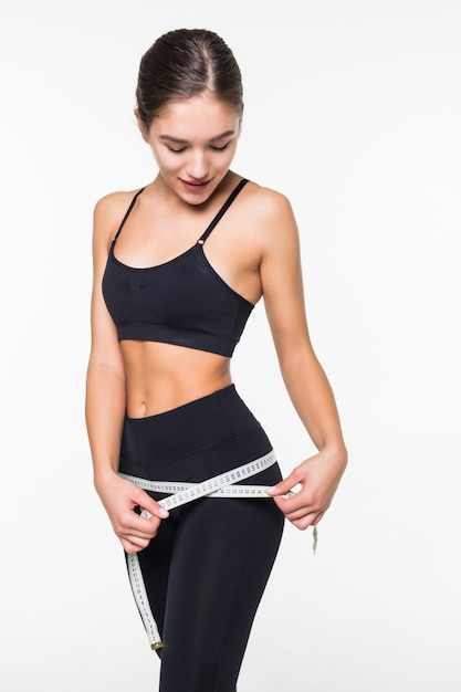 Fitness woman measuring perfect shape of beautiful hips isolated on white wall. healthy lifestyles concept Free Photo