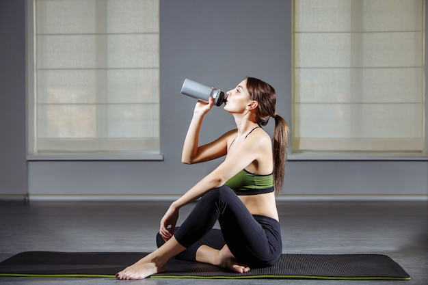 Fitness woman resting after workout in the gym Premium Photo
