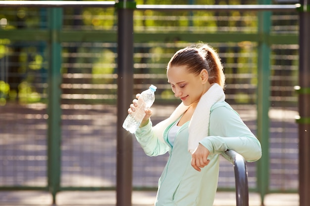 Fitness woman resting after workout, relaxing, drinking clear water from bottle outdoor fitness area in a park Premium Photo