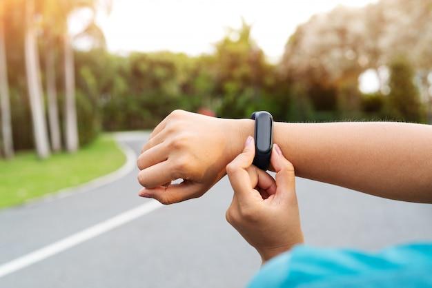 Fitness woman runner setting up smart watch before running Premium Photo