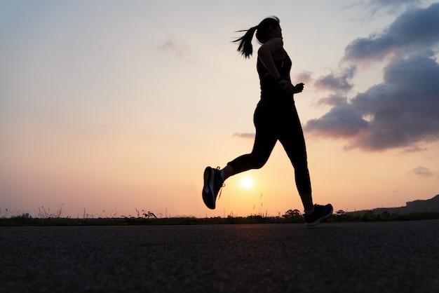 Fitness woman running at sunset Premium Photo