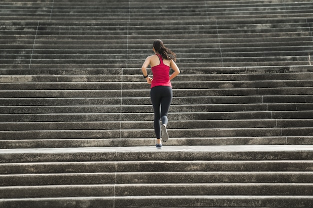 Fitness woman running up the stairs Premium Photo