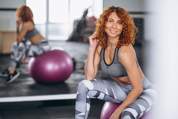 Fitness woman sitting on a fitness ball at the gym Free Photo