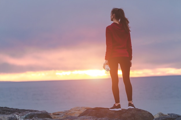 Fitness woman in sneakers standing on a stone, holding a bottle of water and resting after a workout on a sea background at sunset Premium Photo