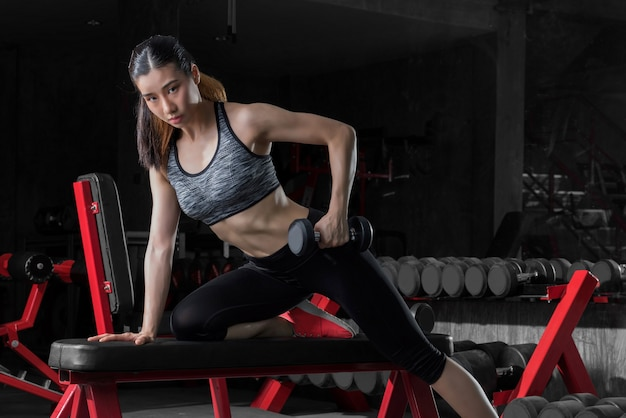 Fitness woman, sporty woman, asian athletic woman pumping up muscles with dumbbells. Premium Photo