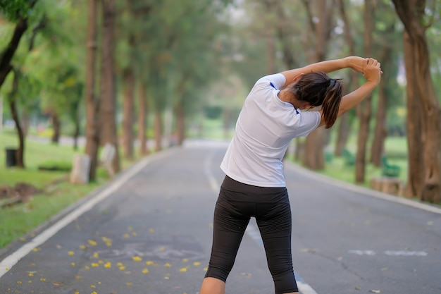 Fitness woman streching in the park, female warm up ready for jogging Premium Photo