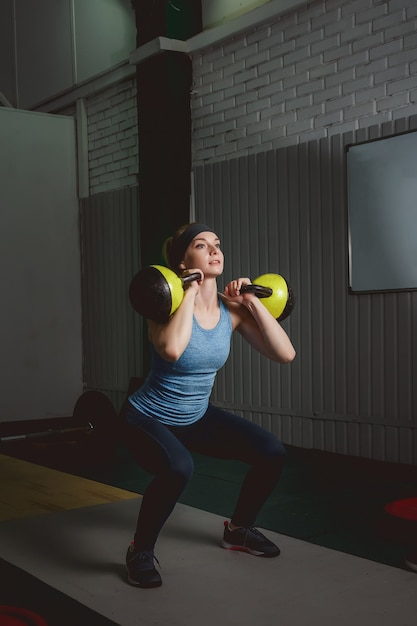 Fitness woman training by kettlebell. fit young lady doing crossfit exercise. Premium Photo