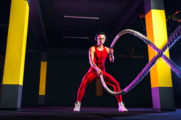Fitness woman using training ropes for exercise at gym. athlete working out with battle ropes at cross gym Premium Photo