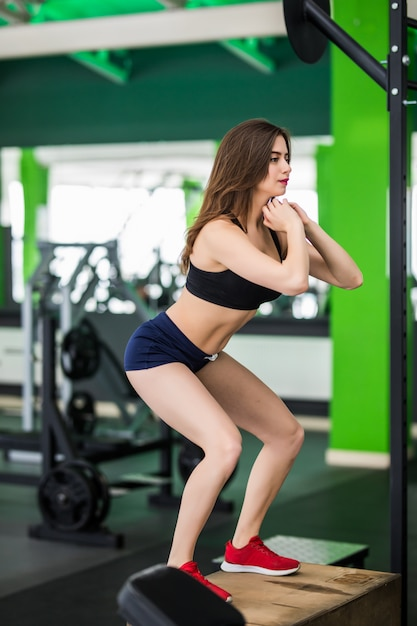 Fitness woman with long hair is working with step box sport simulator in fitness gym Free Photo