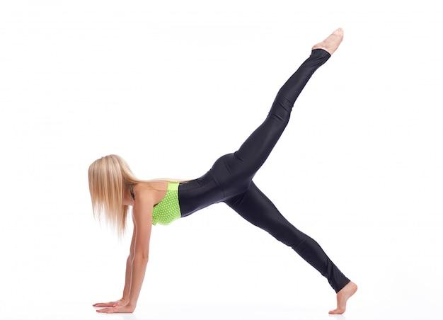 板の運動を行う空気中の彼女の足を持ち上げてストレッチの強いボディを持つフィットネス女性 無料写真
