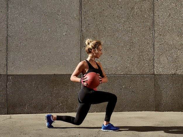Fitness woman working out at outdoors gym using medicine ball. Premium Photo
