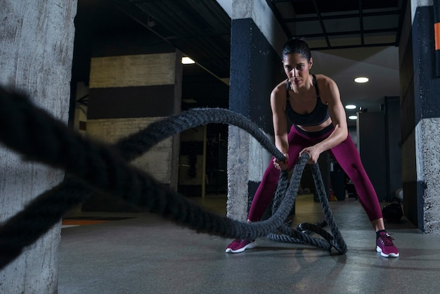 ジムでバトルロープを使って運動するフィットネス女性 無料写真