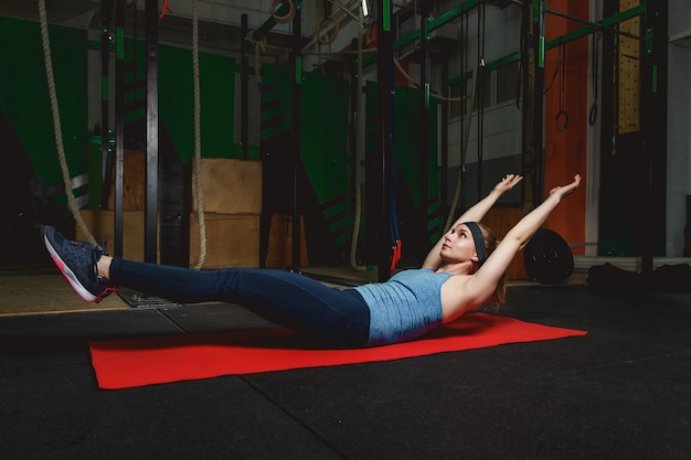 Fitness young girl in the gym doing exercises with abdominals. crossfit Premium Photo