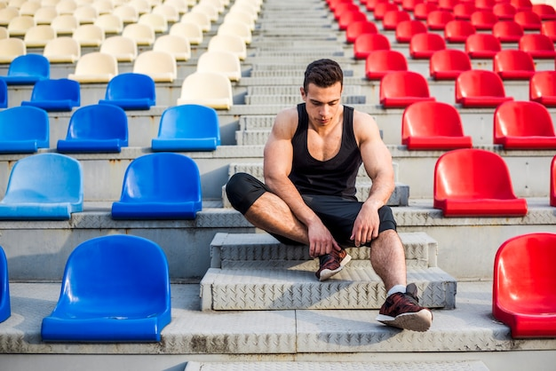 Fitness young male athlete relaxing on the bleacher Free Photo