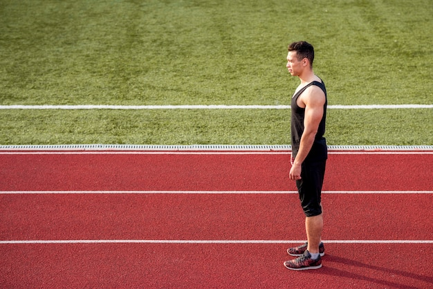 Fitness young male runner standing on red running track Free Photo