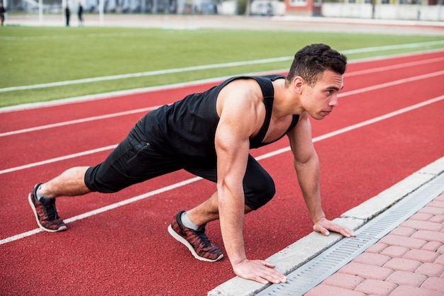 Fitness young man doing pushup on race track Free Photo