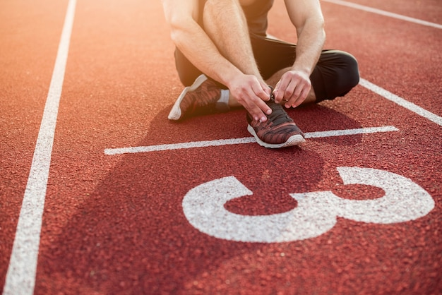 Fitness young man sitting on start line over the red track field Free Photo