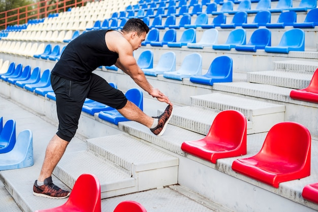 Fitness young man stretching his leg on bleacher Free Photo
