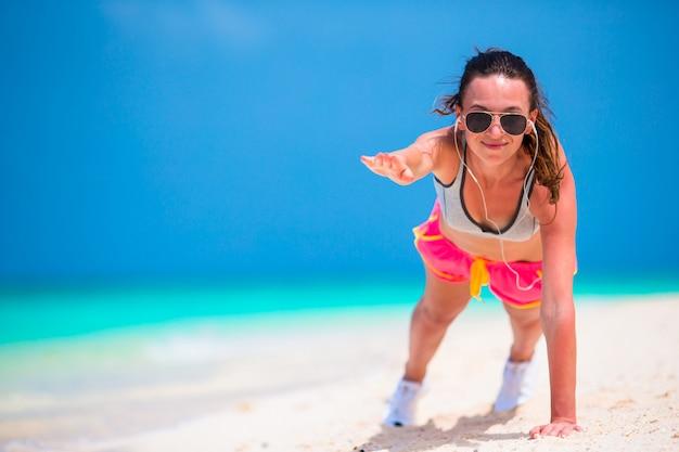 ビーチでプッシュアップ運動を行うフィットネス若い女性 Premium写真