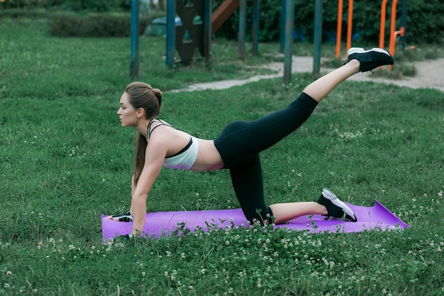 Fitness young woman exercising outdoor in spring park on purple yoga mat Free Photo