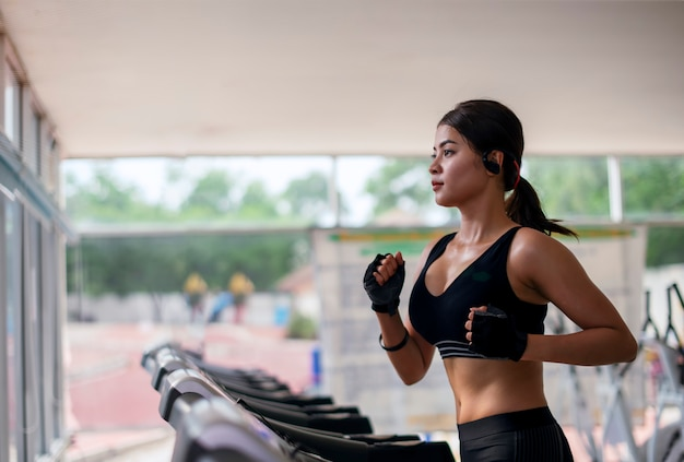 Fitness young woman exercising with listening music and running on treadmill machine in gym Premium Photo