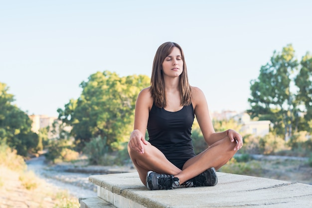 Fitness young woman practices yoga and meditates in the lotus position Premium Photo
