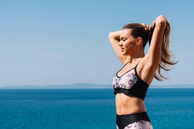 Fitness young woman standing near the blue sea tying her hair Free Photo