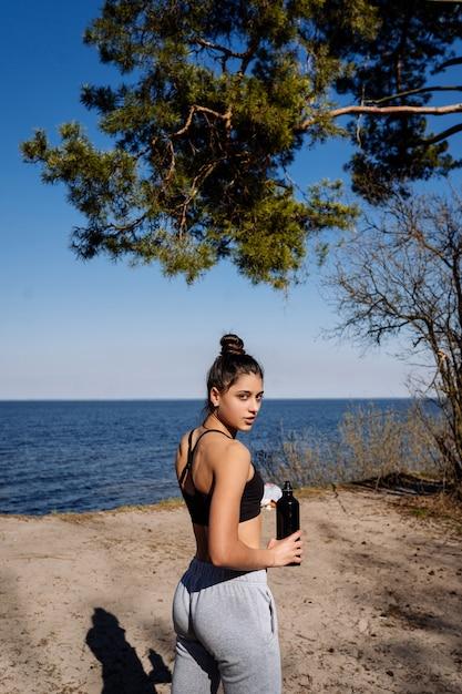 Фитнес молодая женщина гуляет в парке и позирует на камеру Бесплатные Фотографии