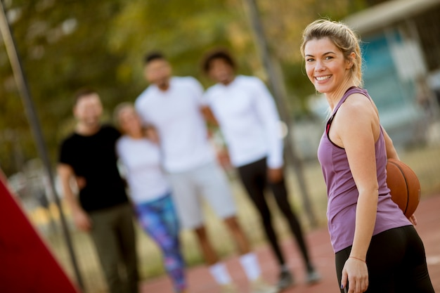 Fitness young woman with basketball ball playing game outdoor with friends Premium Photo
