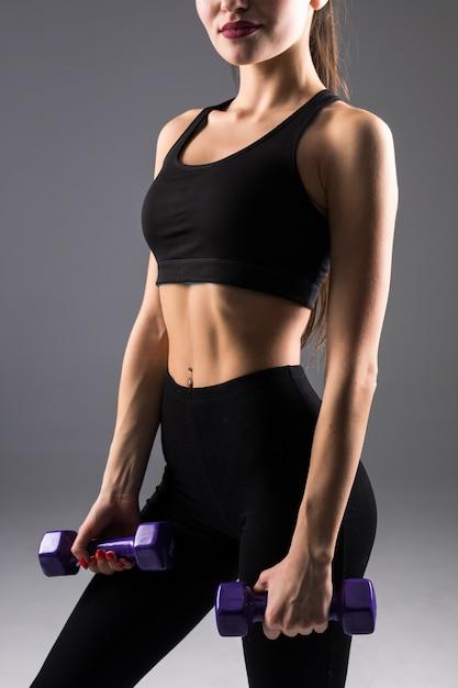 灰色の壁にダンベルを持つフィットネス若い女性。スポーツライフスタイル。 無料写真