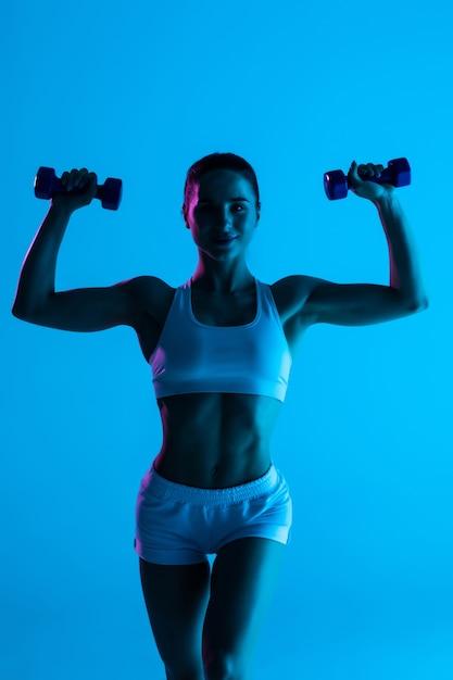 青い明るい背景に分離されたダンベルでワークアウトフィットネス若い女性 Premium写真
