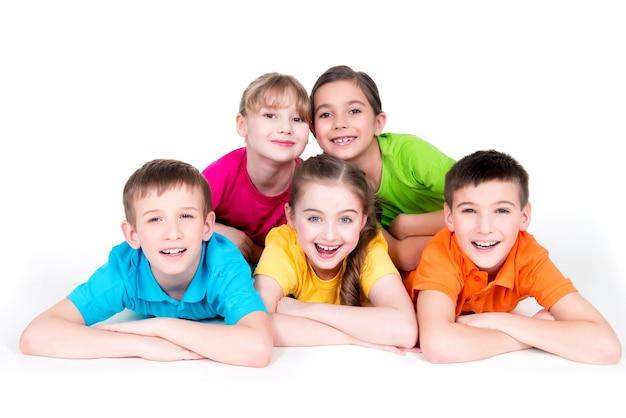 明るくカラフルなtシャツで床に横たわっている5人の美しい笑顔の子供たち-白で隔離。 無料写真
