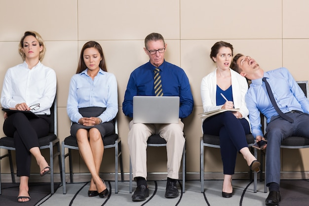 Five Bored Business People Sitting in Waiting Room Free Photo