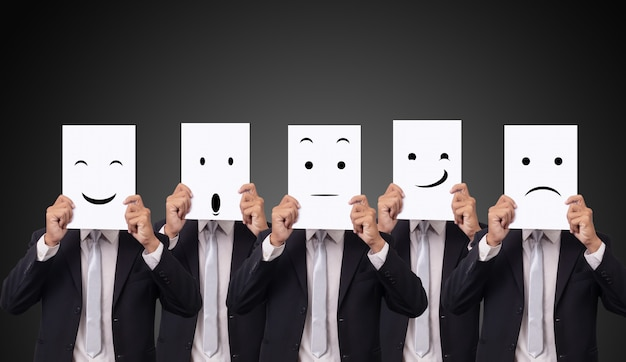 Five businessman holding a card with drawing facial expressions different emotion feelings face on white paper Premium Photo