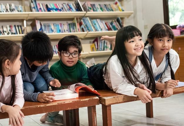 5人の子供が木製の机の上に横たわって、話をして、本を読んで、学校で一緒に活動をしている、レンズフレアエフェクト、ぼやけた光の周り Premium写真