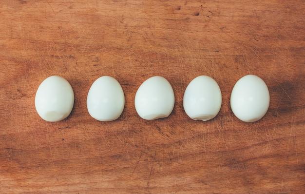 Пять приготовленные очищенные яйца в ряд на старой разделочной доске. вид сверху крупным планом, тонировка фото Premium Фотографии