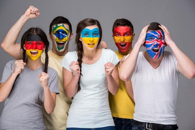 Пять эмоциональных молодых людей с национальными флагами. Premium Фотографии