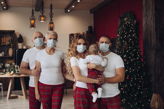 Cinque membri della famiglia con un bambino in maglietta e pantaloni con maschere protettive a natale a casa. Foto Gratuite