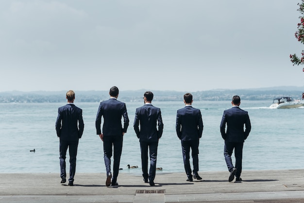 Five men in classy suits walk towards the blue sea Free Photo