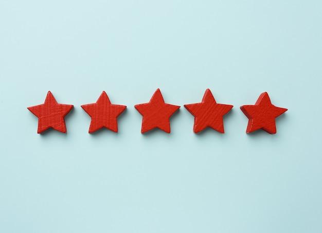 Пять красных деревянных звезд как концепция рейтинга рекордов Premium Фотографии