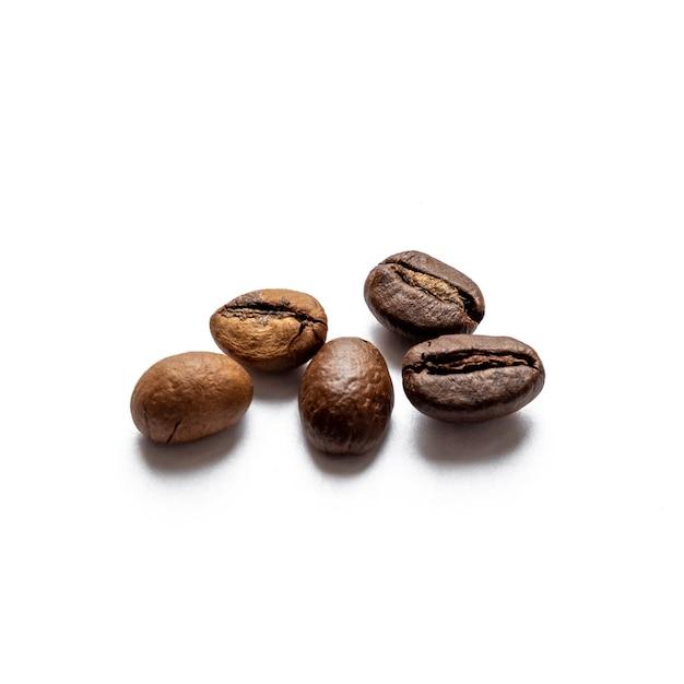 白い表面に散らばった5つの焙煎コーヒー豆 Premium写真