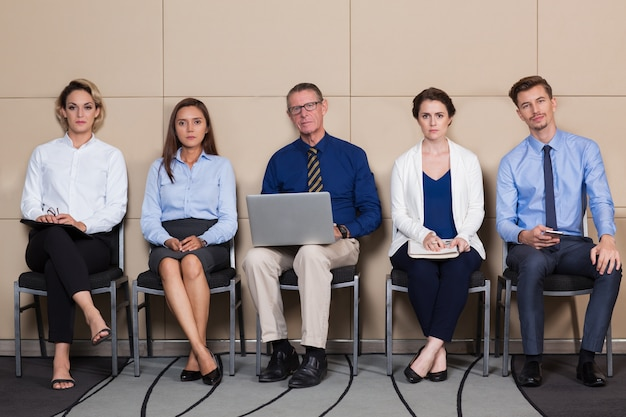 Five Serious Applicants Sitting in Waiting Room Free Photo
